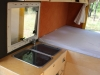 Blick von der Fahrerhaustrenntür auf die Küche, den Kühlschrank und die Hängeschränke